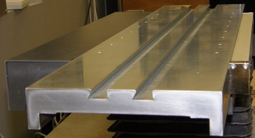 Hard chrome plated X-axis stage, made of hardened tooling steel and with dual standard dovetail grooves for easy part fixturing on a Digital Optical Comparator